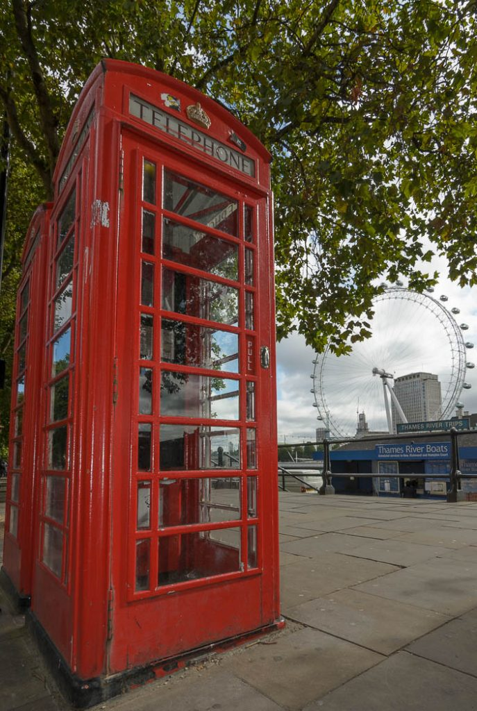A traditional red phone box with the London eye in the background.