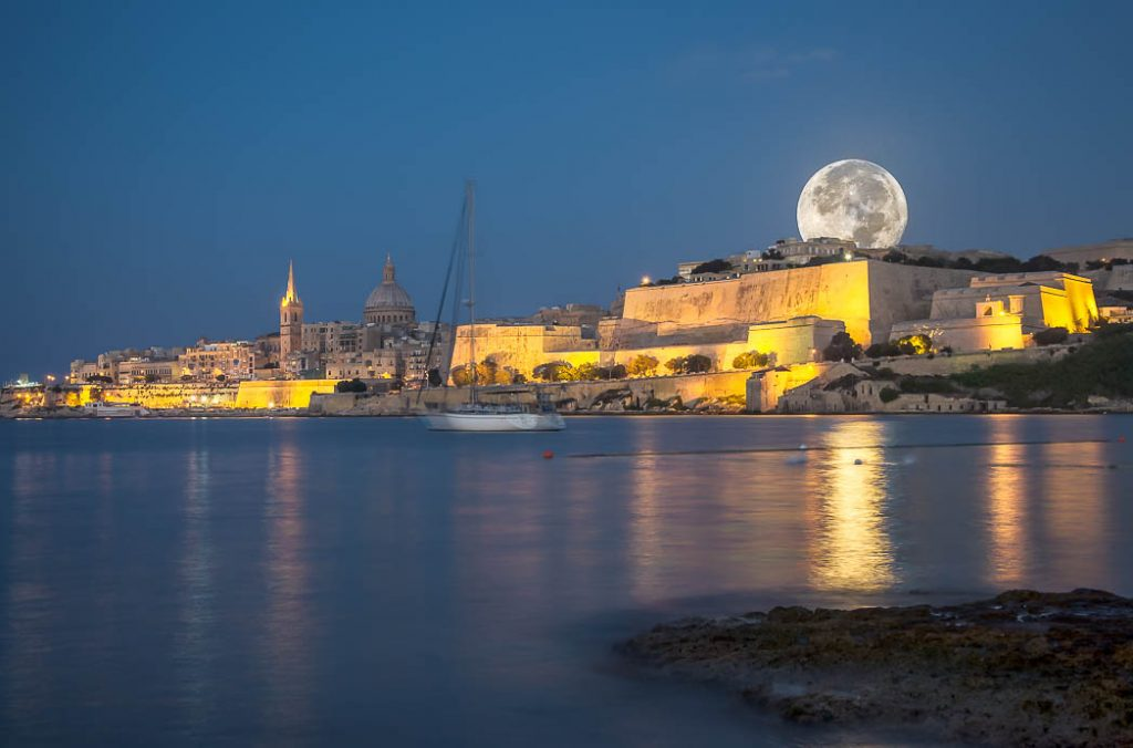 Valetta, the capital of Malta with a moon rising behind it.