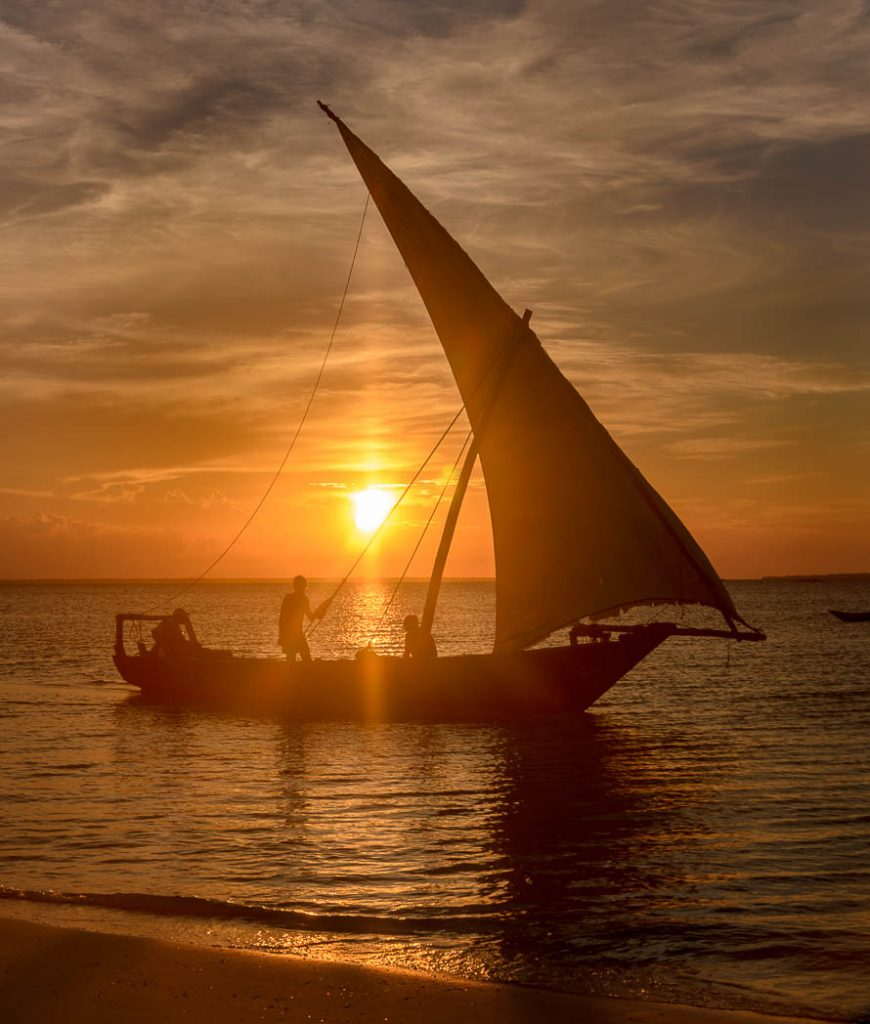 A traditional boat sails at dusk beside the spice island of Zanzibar